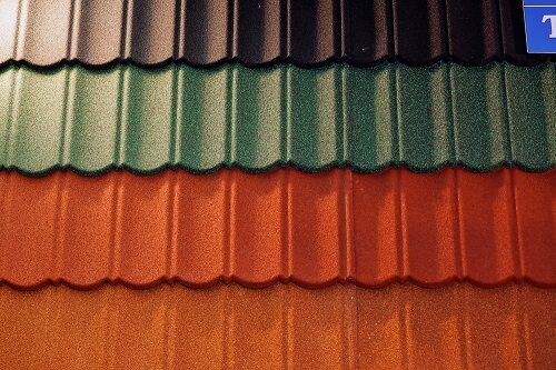 Selection of different roof tiles, including brown, red and green tiles