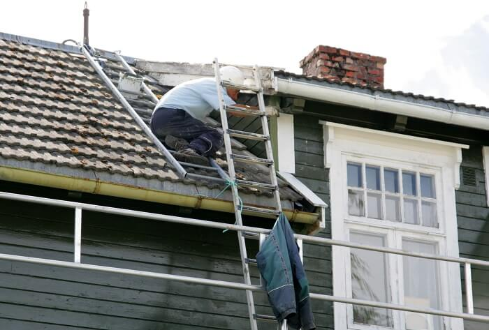 A man painting roof of a house