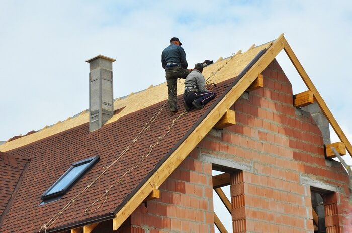 Two men installing a roof