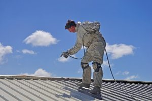 Roof painter wearing safety gear and spraying a metal roof.