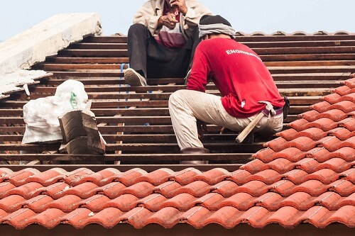 Workers replacing clay tiles on a roof